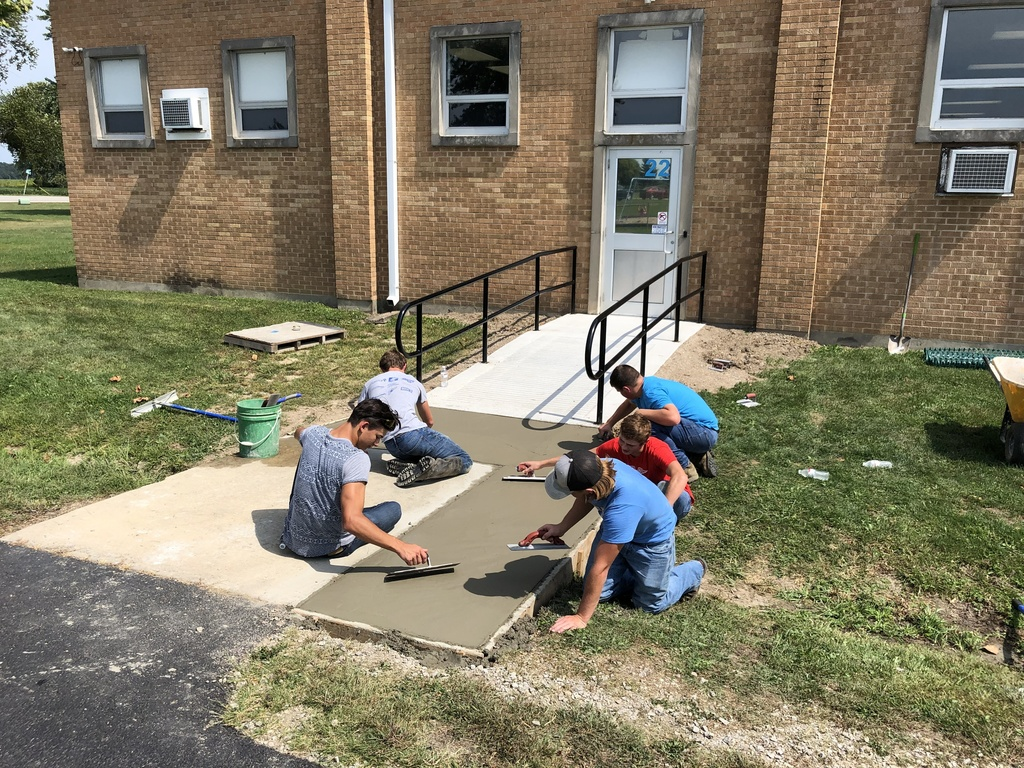 Mr. Owen and his construction skills class working on the sidewalk